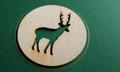 Weihnachtskarte mit gelaserter Holzapplikation in Form eines Hirsches.